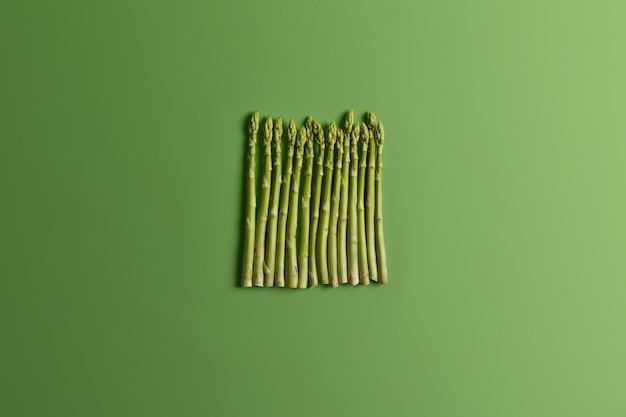 녹색 배경에 세로로 배열 된 아스파라거스의 플레이 레이. 식품 및 유기 영양 개념. 상위 뷰, 먹는 신선한 생 야채. 봄 시즌, 새로운 수확. 요리 재료