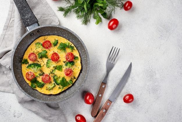 Флай лежал завтрак омлет в кастрюле с помидорами и столовыми приборами