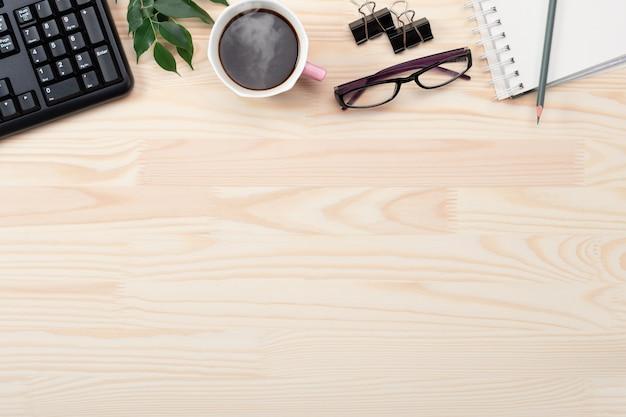 オフィステーブルデスクのフレイレイ。緑の葉、メモ帳、木製のテーブルにコーヒーとフェミニンなデスクワークスペースフレーム。