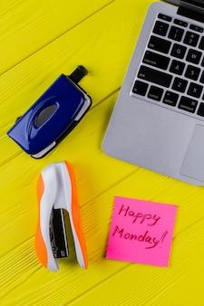노란색 나무 테이블에 사무용 액세서리를 깔아보세요. 스테이플러와 행복한 월요일 소원이 있는 노트북.