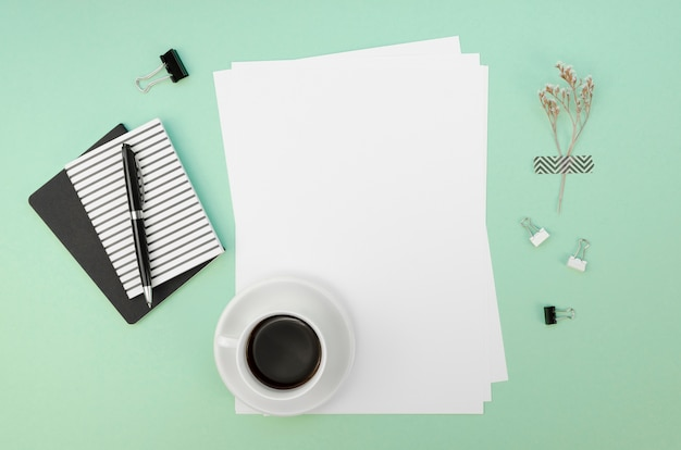 Flay lay of papers on desk with pen and coffee cup