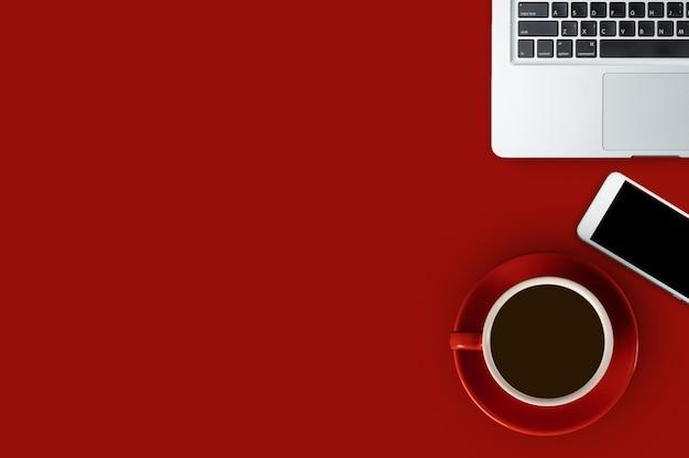 플래이는 노트북, 스마트폰, 블랙 커피 한 잔이 있는 빨간 책상, 복사 공간이 있는 위쪽 전망
