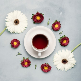 Flay lay tea cup of fruits and arrangement of daisies
