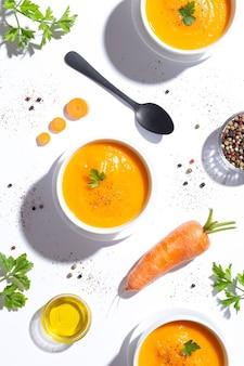 Свежее лежал, три миски морковного супа и одна морковь на белом фоне Premium Фотографии