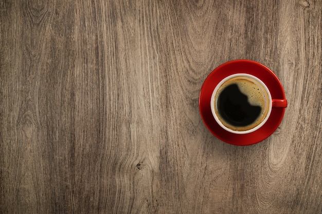 Flay lay wooden desk red cup of black coffee, top view with copy space on wooden table