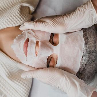 Flay lay di giovane donna che ottiene un trattamento con maschera per la pelle