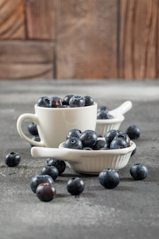 Fleshy blueberries in cup and ladles side view on grey surface