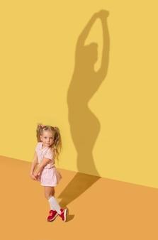 유연성과 유명합니다. 어린 시절과 꿈의 개념. 자녀와 함께 개념적 이미지입니다. 스튜디오 벽에 그림자가 그려져 있습니다. 어린 소녀는 발레리나, 발레 댄서, 연극 예술가가되기를 원합니다.
