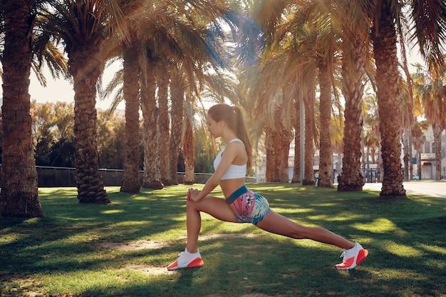 柔軟性。屋外でウォーミングアップしながらストレッチスポーツウェアの美しい若い女性