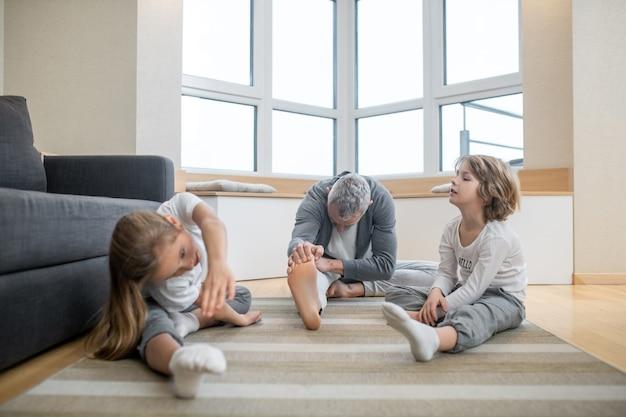 유연성 운동. 집에서 바닥에 앉아 유연성 워밍업을 하는 편안한 옷을 입은 어린 아이들과 성인 백발 아빠