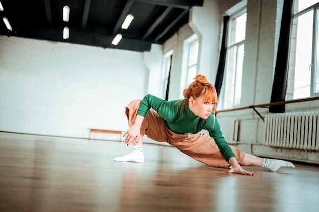 柔軟性。柔軟性のためにアーサナをしている緑のタートルネックを身に着けているプロのヨガコーチ