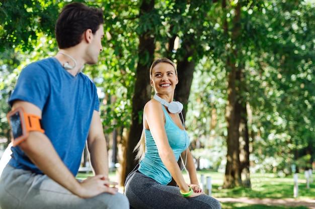 柔軟性トレーニング。柔軟性トレーニングをしながら彼女のボーイフレンドに微笑んで陽気なスポーティーな女性