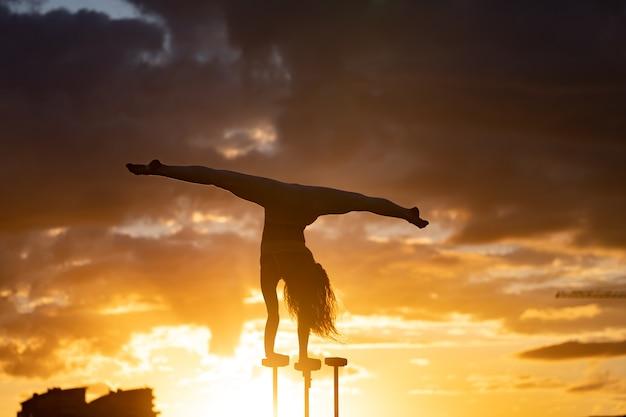 劇的な日没時に街並みの背景に逆立ちを行う柔軟な曲芸師