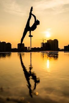 극적인 일몰 동안 도시 경관 배경에서 물구나무서기를 하는 유연한 곡예사