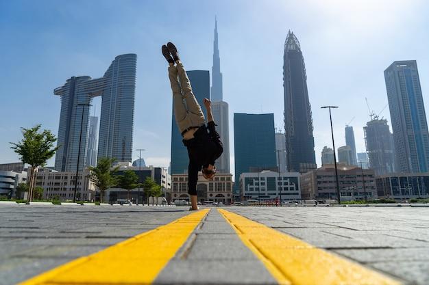 Гибкий acrobat удерживает равновесие на одной руке с размытым городским пейзажем дубая.