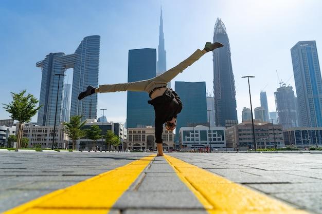 Гибкий acrobat удерживает равновесие на одной руке с размытым городским пейзажем дубая. Premium Фотографии