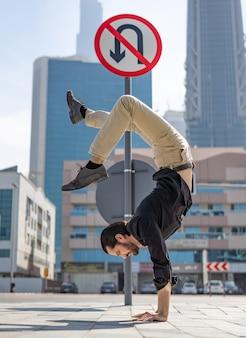 Гибкий acrobat держит равновесие на руках с размытым городским пейзажем дубая, а разворот запрещен.