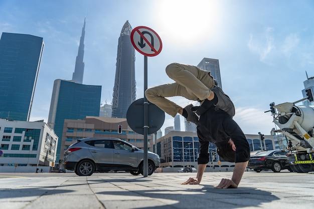 Гибкий акробат держит равновесие на руках с размытым городским пейзажем дубая и дорожным знаком утурн пр ...