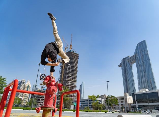 유연한 acrobat은 흐린 두바이 도시 풍경으로 소방 소화전에서 한 손으로 균형을 유지합니다.