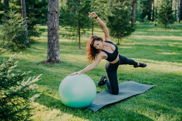 Flexible active woman in sportsclothes makes fitness exercises on karemat with fitball