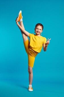 Гибкая очаровательная девочка в желтой спортивной одежде выполняет поперечный шпагат