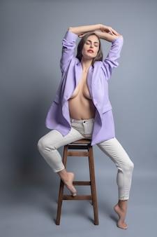 柔軟でフェミニン。裸足で椅子に座ってポーズを美しく湾曲した開いたpidakで目を閉じて若いきれいな女性