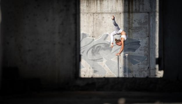버려진 건물에서 균형을 유지하는 그녀의 손에 서있는 유연하고 맞는 소녀