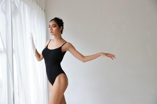 Flexible asian ballet dancer stretching on white wall studio