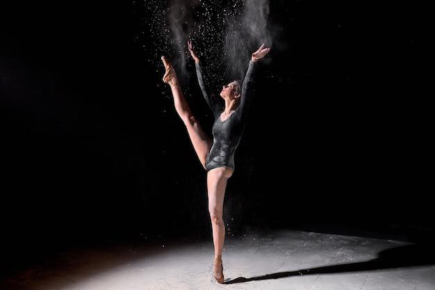 黒のボディスーツとトウシューズを身に着けて、黒のスタジオの背景に踊り、小麦粉を振りかける柔軟なバレリーナの女性。優雅に動く魅力的な白人女性の全身像