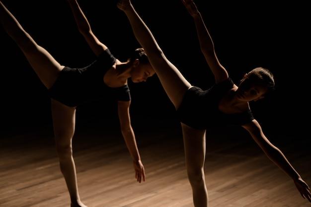 Flexible ballerinas stretch on a dark lighted scene