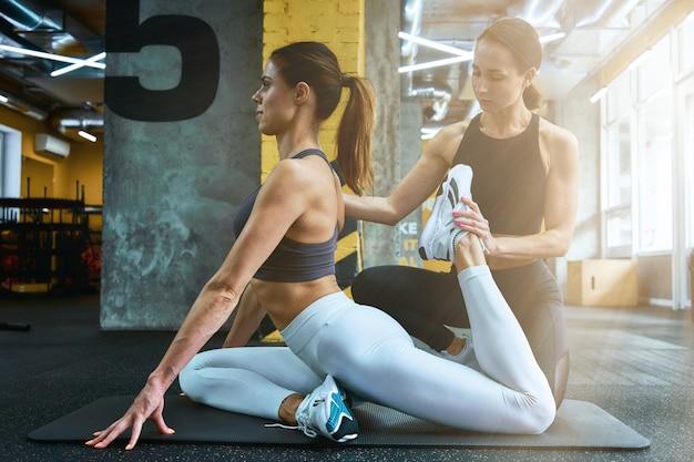유연한 몸. 체육관에서 개인 트레이너의 도움을 받아 스트레칭 운동을 하는 젊고 아름다운 여성의 옆모습, 운동 전후 워밍업. 스포츠와 건강한 라이프 스타일