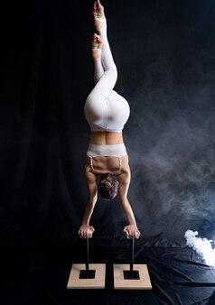 Гибкая цирковая артистка-акробат делает стойку на руках на спине и курит