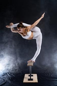 柔軟なサーカスアーティスト-背中と喫煙者に逆立ちをしている女性の曲芸師