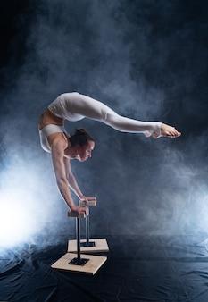 Гибкая артистка цирка - женщина-акробат делает стойку на руках на спине и курильщик