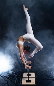 Гибкая цирковая артистка-акробат делает стойку на руках