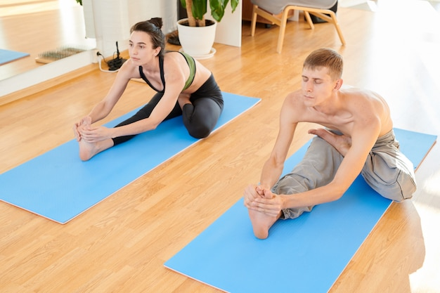 Flexible couple stretching bodies at yoga class
