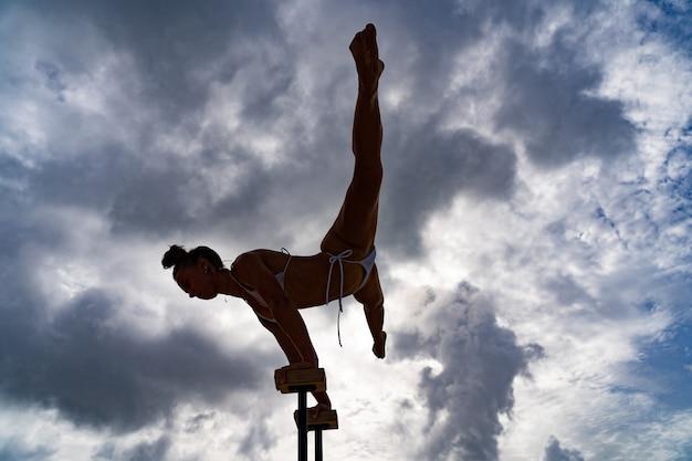 Гибкая цирковая артистка делает стойку на руках против удивительной мотивационной страсти и концепции достижений