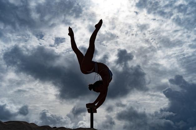 Гибкая цирковая артистка делает стойку на руках на фоне удивительных облаков. концепция силы воли, потенциала и желания.