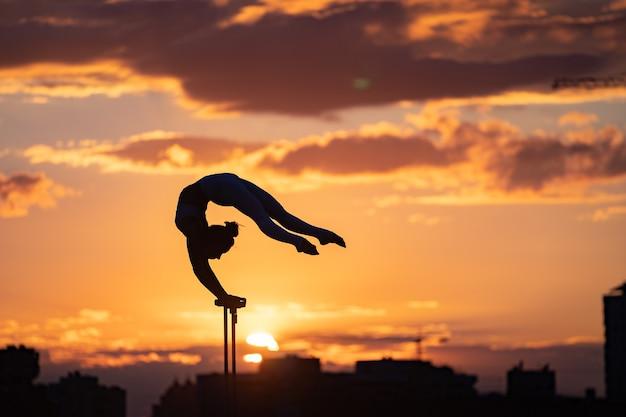 柔軟な女性サーカスアーティストは、劇的な夕日と街並みに対してバランスを保ち、屋上でゆがみをします