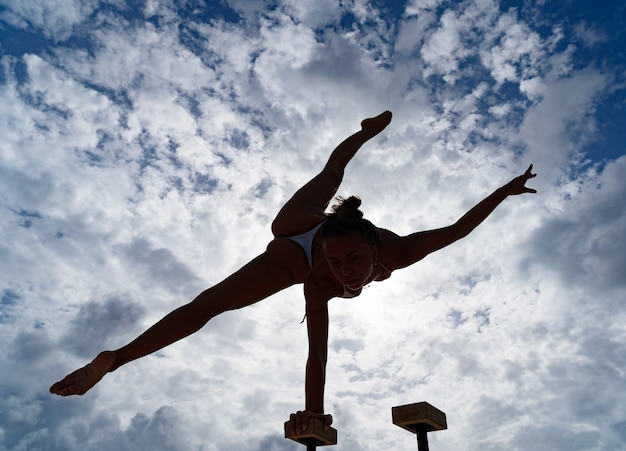 Гибкая артистка цирка удерживает равновесие одной рукой на фоне удивительных облаков. концепция силы воли, потенциала и желания.