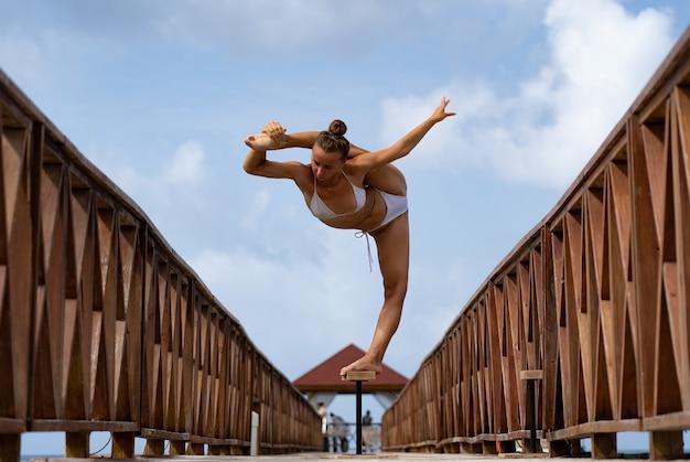 Гибкая артистка цирка удерживает равновесие в шпагате на мосту. концепция здорового образа жизни, йоги и гибкости. Premium Фотографии