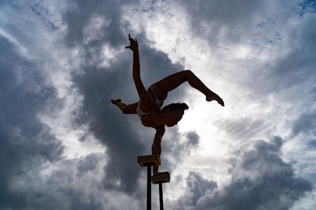 Гибкая цирковая артистка держит баланс на руках на фоне удивительной индивидуальности и оригинальности облачного ландшафта.