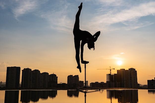 Гибкая артистка цирка одной рукой удерживает равновесие на крыше на фоне драматического заката и ...