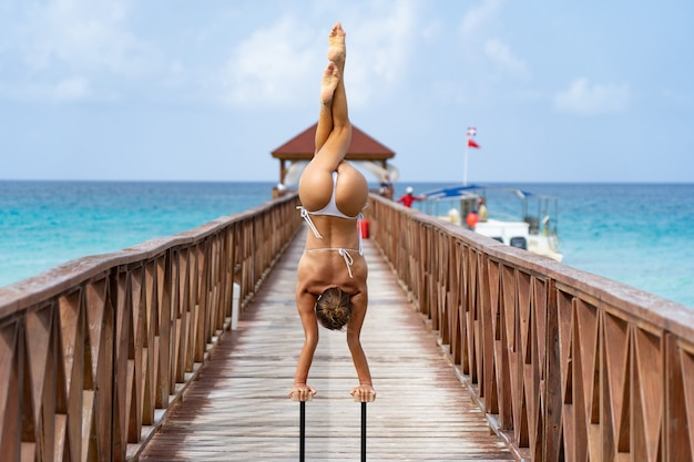 Гибкий женский цирк делает стойку на руках вверх ногами на пирсе с фоном неба. путешествия и отдых и концепция здорового образа жизни.