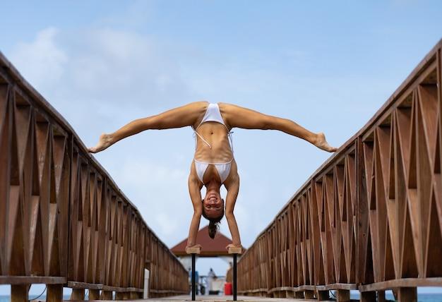 Гибкий женский цирк делает стойку на руках вверх ногами на пирсе