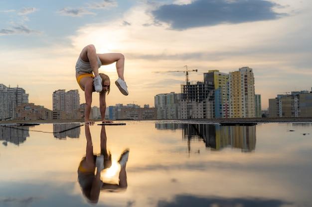 유연한 여성 체조 선수는 물구나무서기 운동을 하고 도시 경관 바에서 물에 반사되어 있습니다.