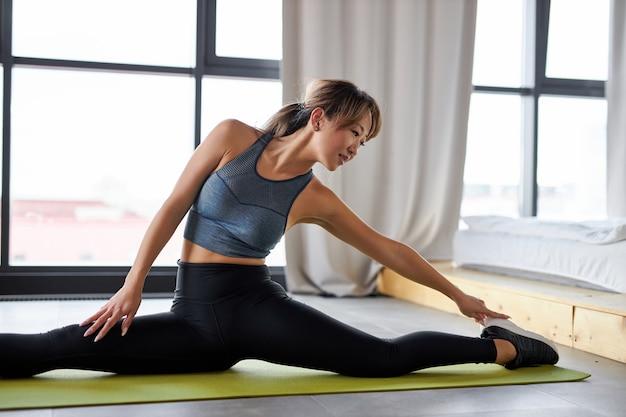 体を伸ばすスポーツ服を着た柔軟な女性は、自宅で一人でトレーニングを楽しんだり、検疫中に部屋でスポーツトレーニングをしたりします。ヨガマットの上で部屋で運動する