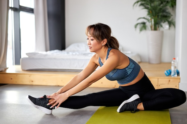 Flexible female in sportive outfit stretching body, enjoy workout at home alone, doing sport workout in room during quarantine. exercising in room on yoga mat
