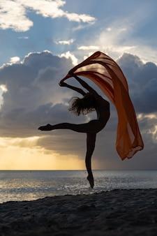 Женщина с гибкой крой, прыгающая с шелком во время драматического заката с грозовыми облаками, концепция стремления и возможностей