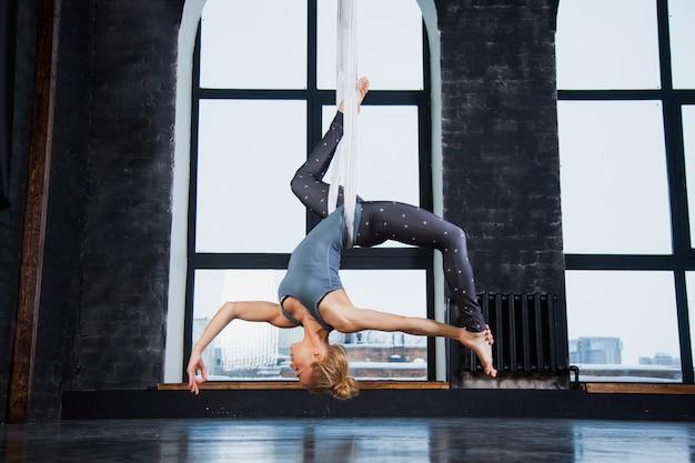 Гибкая посадка молодая спортивная женщина практикует воздушную йогу в гамаке